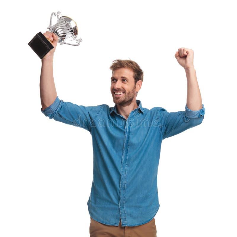 Το άτομο που κρατά ένα τρόπαιο γιορτάζει την επιτυχία και κοιτάζει στην πλευρά στοκ φωτογραφίες