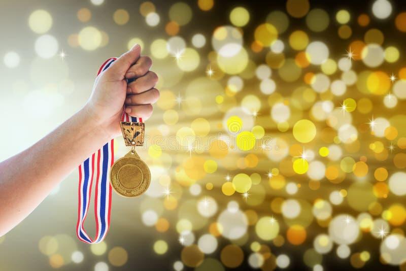 Το άτομο που κρατά ψηλά ένα χρυσό μετάλλιο ενάντια, κερδίζει την έννοια στοκ φωτογραφίες