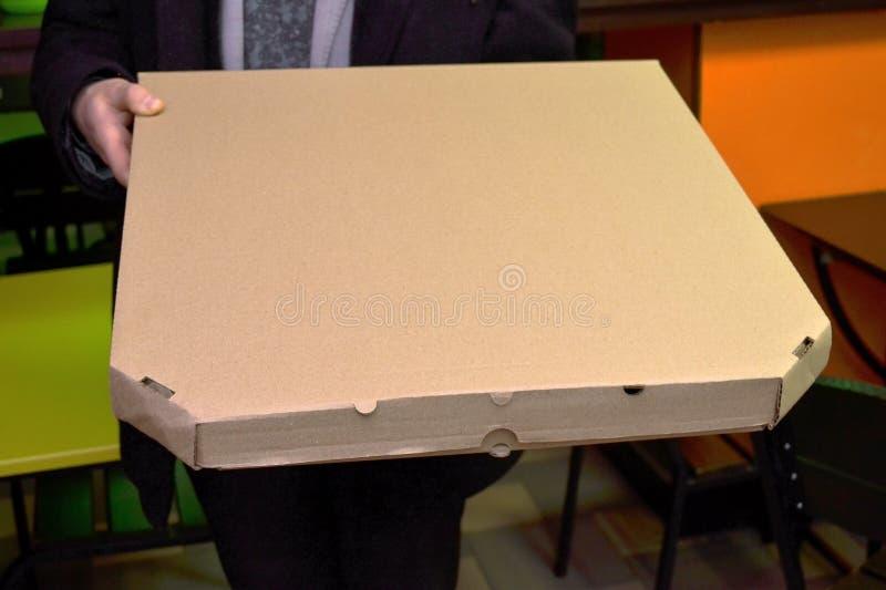 Το άτομο που παραδίδει την πίτσα κρατά ένα μεγάλο κιβώτιο με ένα μέγεθος πιτσών 50 εκατοστόμετρων ή 20 ιντσών στοκ φωτογραφία με δικαίωμα ελεύθερης χρήσης