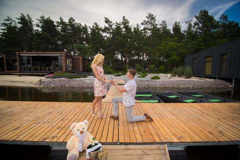Το άτομο που στέκεται σε μια αποβάθρα στο γόνατο κάνει μια πρόταση γάμου στοκ φωτογραφία με δικαίωμα ελεύθερης χρήσης