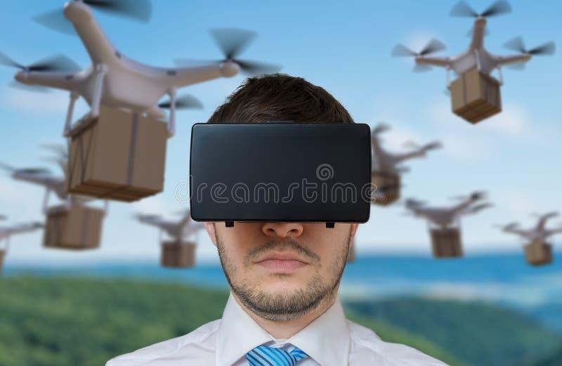 Το άτομο που φορά την κάσκα εικονικής πραγματικότητας ελέγχει πολλούς πετώντας κηφήνες στοκ εικόνες