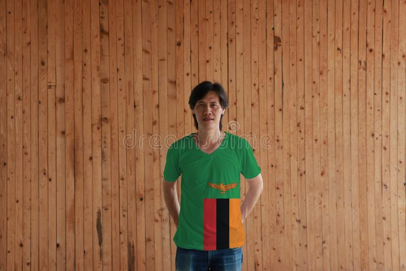 Το άτομο που φορά το χρώμα σημαιών της Ζάμπια του πουκάμισου και που στέκεται με διασχισμένος πίσω από τον πίσω δίνει στο ξύλινο  στοκ φωτογραφία με δικαίωμα ελεύθερης χρήσης