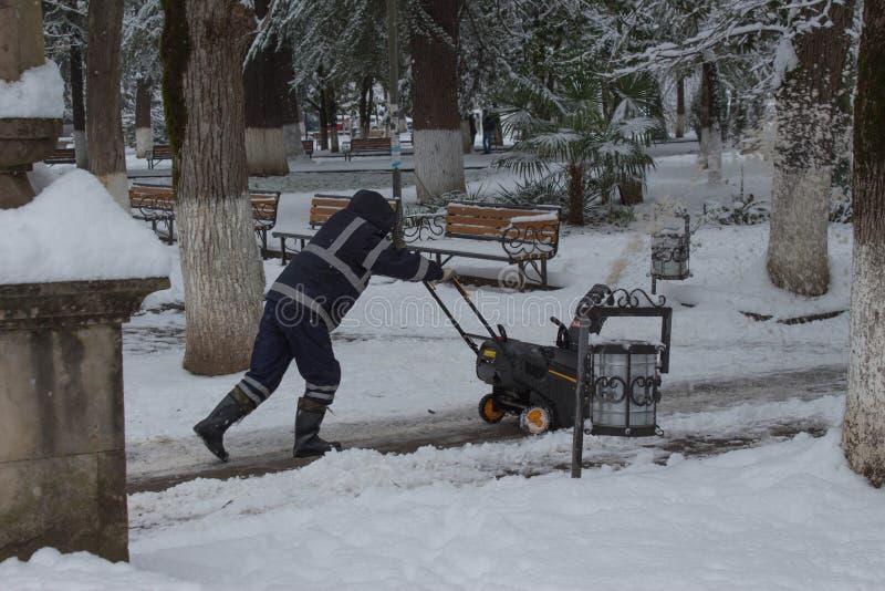 Το άτομο που χρησιμοποιεί μια μηχανή ρίψης χιονιού μια χειμερινή ημέρα μετά από μια χιονοθύελλα πέταξε 8 ίντσες του χιονιού στοκ φωτογραφίες με δικαίωμα ελεύθερης χρήσης