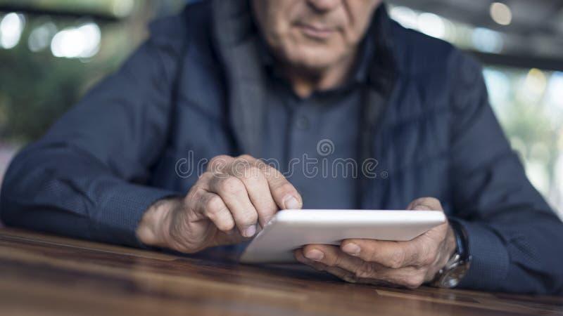 Το άτομο που χρησιμοποιεί την ψηφιακή ταμπλέτα κοντά επάνω βλέπει στοκ εικόνα με δικαίωμα ελεύθερης χρήσης