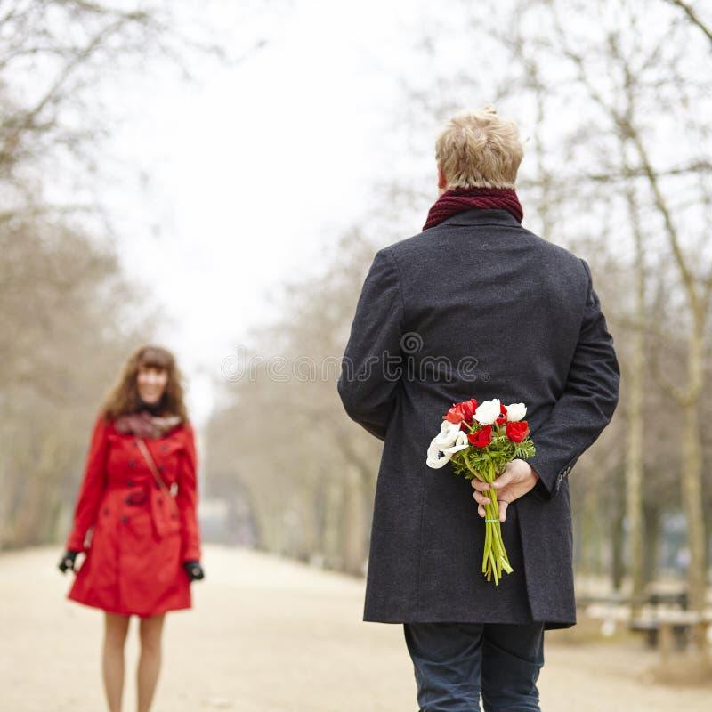 Το άτομο πρόκειται να προσφέρει τα λουλούδια στη φίλη του στοκ εικόνες