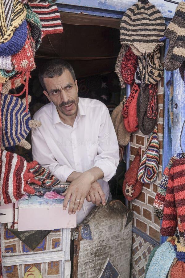 Το άτομο πωλεί ζωηρόχρωμο πλέκει τα μαντίλι και τα καπέλα σε Chefchaouen, Μαρόκο στοκ εικόνα