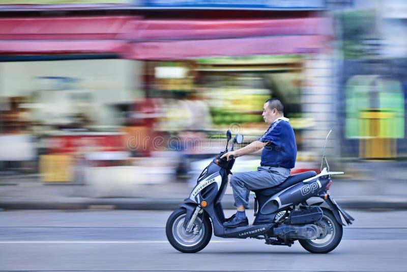 Το άτομο σε ένα μηχανικό δίκυκλο αερίου περνά ένα κατάστημα φρούτων, Σαγκάη, Κίνα στοκ φωτογραφία με δικαίωμα ελεύθερης χρήσης