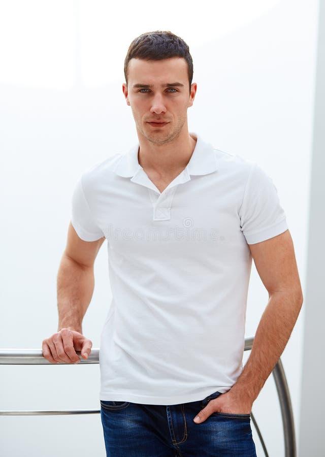 Το άτομο σε ένα πουκάμισο πόλο στέκεται στο κιγκλίδωμα στοκ εικόνα