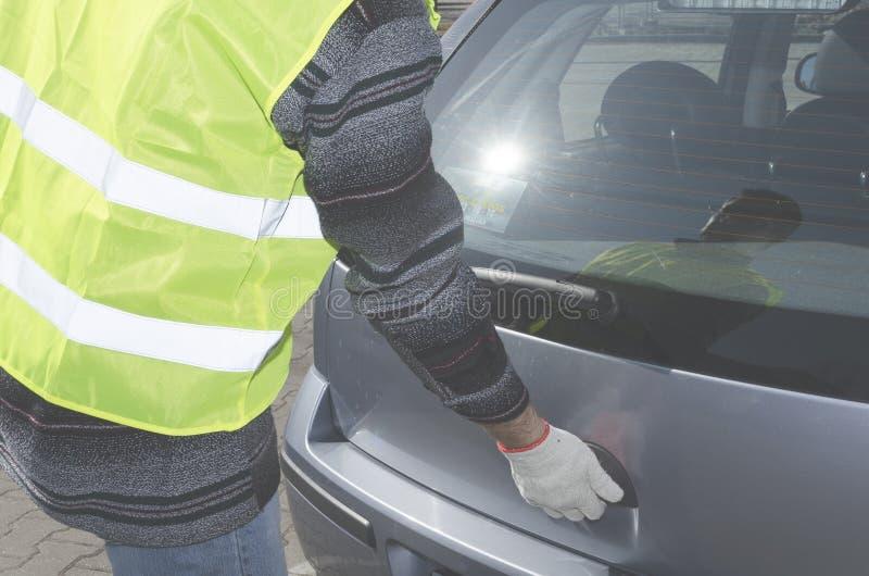Το άτομο σε μια φανέλλα ασφάλειας ανοίγει την μπότα στο αυτοκίνητό του στοκ φωτογραφία με δικαίωμα ελεύθερης χρήσης