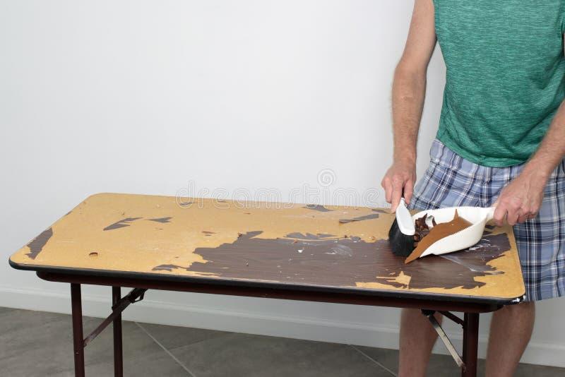 Το άτομο σκουπίζει τα συντρίμμια από να ξαναέρθει στην επιφάνεια He's επιτραπέζιων κορυφών στοκ εικόνες