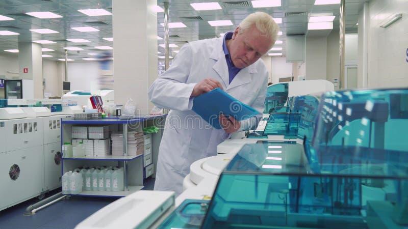 Το άτομο στέκεται κοντά στις εργαστηριακές συσκευές στοκ εικόνες
