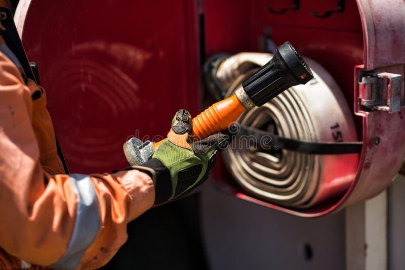 Το άτομο στα γάντια ασφάλειας και την πορτοκαλιά φόρμα παίρνει το ακροφύσιο πυρκαγιάς στοκ φωτογραφίες