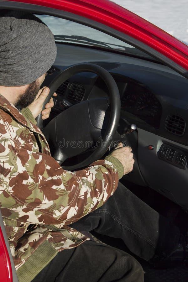 Το άτομο στην ΚΑΠ βάζει τα κλειδιά στην ανάφλεξη του αυτοκινήτου στοκ φωτογραφίες