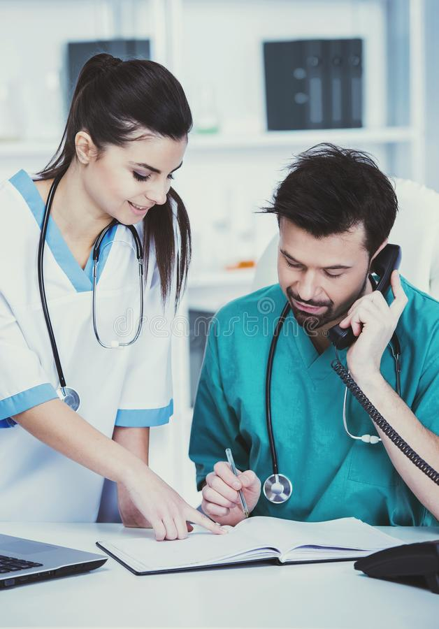 Το άτομο στην πράσινη ιατρική εσθήτα επιδέσμου μιλά στο τηλέφωνο στοκ εικόνες
