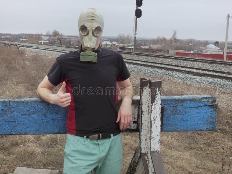 Το άτομο στη μάσκα αερίου στο αδιέξοδο του σιδηροδρόμου Δείξτε το δάχτυλο ότι όλο είναι καλά στοκ φωτογραφία με δικαίωμα ελεύθερης χρήσης
