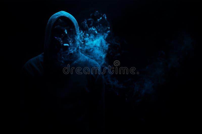 Το άτομο στη μαύρη κουκούλα στο σκοτάδι νύχτας άναψε dimly, έννοιες του δ στοκ εικόνα με δικαίωμα ελεύθερης χρήσης