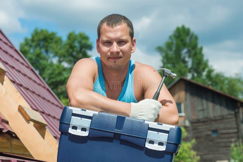 Το άτομο στη στέγη στο κιβώτιο με το εργαλείο στοκ φωτογραφίες με δικαίωμα ελεύθερης χρήσης