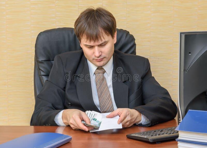 Το άτομο στο γραφείο βάζει τα χρήματα σε έναν φάκελο στοκ εικόνα