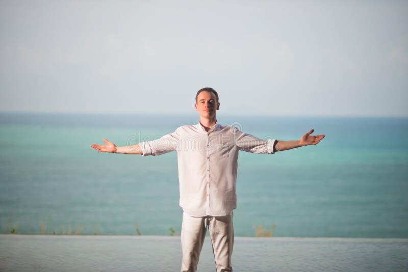 Το άτομο στο λευκό ντύνει τη στάση σε ένα υπόβαθρο του ωκεανού με τα διαζευγμένα χέρια στην πλευρά, απολαμβάνοντας της ελευθερίας στοκ φωτογραφίες
