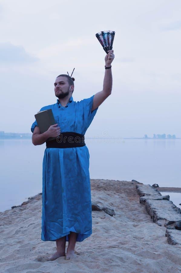 Το άτομο στο μπλε κιμονό με το κουλούρι τρίχας που στέκεται και που κρατά τον ανεμιστήρα βιβλίων και χεριών μέσα το χέρι και το κ στοκ φωτογραφία με δικαίωμα ελεύθερης χρήσης