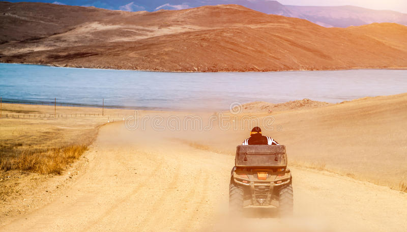 Το άτομο στο ποδήλατο τετραγώνων οδηγά στο δρόμο αμμοχάλικου στοκ εικόνα
