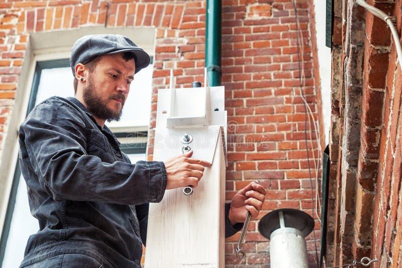 Το άτομο σφίγγει ένα καρύδι σε μια άσπρη δομή μετάλλων στοκ φωτογραφία με δικαίωμα ελεύθερης χρήσης