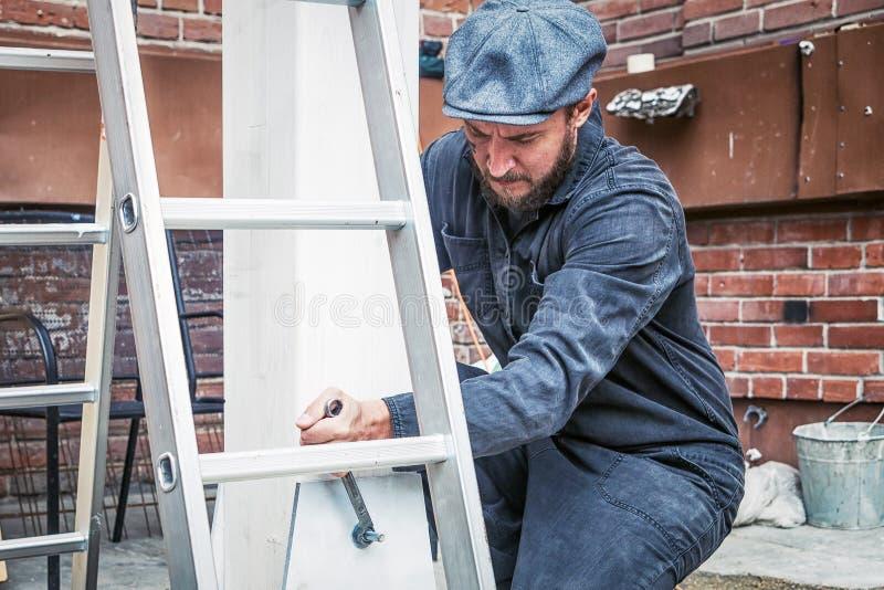 Το άτομο σφίγγει τα mettalical καρύδια με ένα γαλλικό κλειδί στοκ εικόνα με δικαίωμα ελεύθερης χρήσης