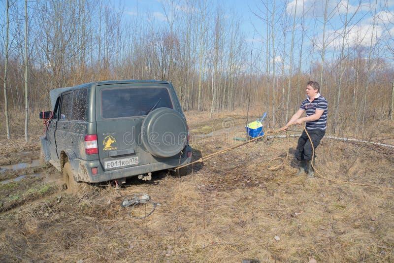 Το άτομο σφίγγει το σχοινί για την εξαγωγή που κολλιέται στον UAZ-πατριώτη λάσπης στοκ εικόνα με δικαίωμα ελεύθερης χρήσης