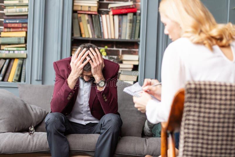 Το άτομο σχετικά με το κεφάλι του ενώ συναίσθημα τρομοκράτησε την κατοχή πολλών προβλημάτων στοκ φωτογραφία με δικαίωμα ελεύθερης χρήσης
