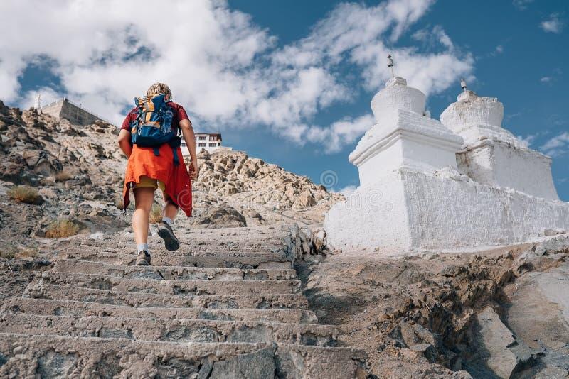 Το άτομο τουριστών αναρριχείται επάνω στα σκαλοπάτια στο θιβετιανό ιερό μέρος στο Ιμαλάια μ στοκ εικόνες