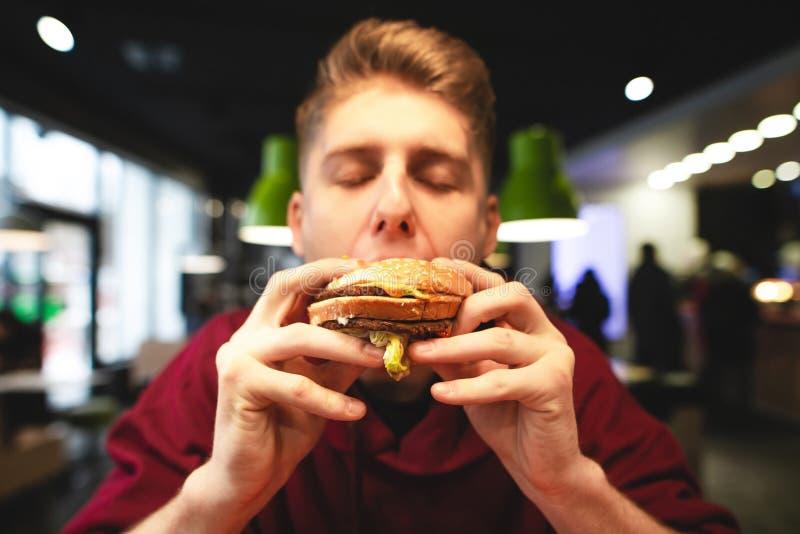 Το άτομο τρώει εύγευστο μεγάλο burger με τις προσοχές του ιδιαίτερες και τις απολαύσεις Πορτρέτο κινηματογραφήσεων σε πρώτο πλάνο στοκ εικόνες με δικαίωμα ελεύθερης χρήσης