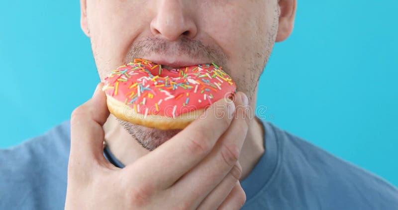 Το άτομο τρώει doughnut την κινηματογράφηση σε πρώτο πλάνο σε ένα μπλε υπόβαθρο στοκ φωτογραφία με δικαίωμα ελεύθερης χρήσης