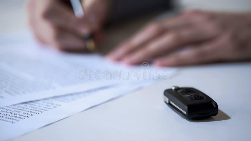 Το άτομο υπογράφει τα έγγραφα για την αγορά αυτοκινήτων ή το μίσθωμα, αυτόματες ασφαλιστικές υπηρεσίες, κλειδί στον πίνακα στοκ εικόνες