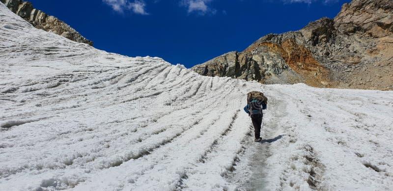 Το άτομο φέρνει τον περίπατο τσαντών στον παγετώνα στο πέρασμα chommala στον τρόπο στο πιό everest στρατόπεδο βάσεων στο Νεπάλ στοκ φωτογραφίες