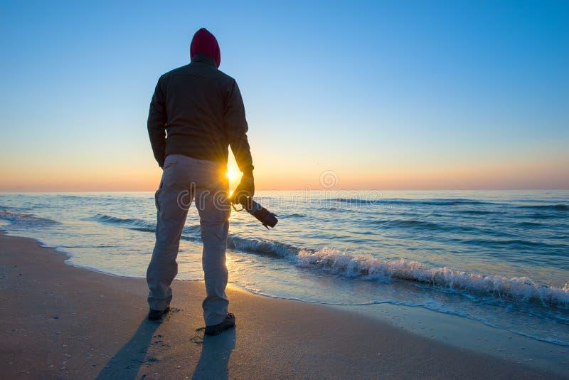 Το άτομο φωτογραφίζει μια ανατολή ενάντια στη θάλασσα στοκ εικόνα