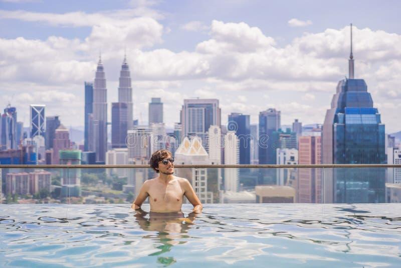 Το άτομο χαλαρώνει στην πισίνα στην ανατολή, στη στέγη στην πόλη Πλούσιοι άνθρωποι στοκ εικόνες με δικαίωμα ελεύθερης χρήσης