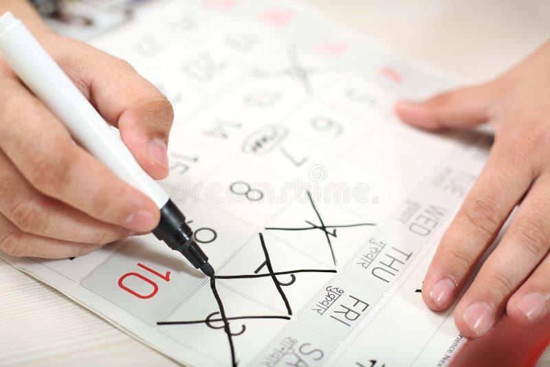 Το άτομο χαρακτηρίζει τις διαγώνιες ημέρες στο ημερολόγιο με το δείκτη στοκ εικόνα
