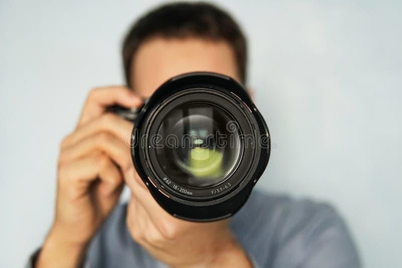Το άτομο χρησιμοποιεί την επαγγελματική κάμερα με το φακό telephoto στοκ φωτογραφία με δικαίωμα ελεύθερης χρήσης