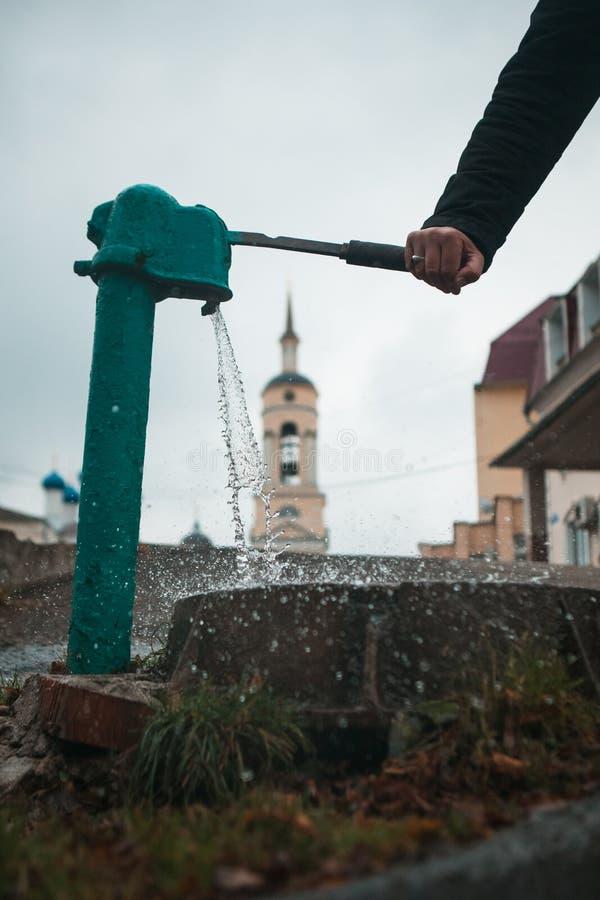 Το άτομο χύνει ένα φλυτζάνι του νερού από το γερανό στηλών στοκ φωτογραφία με δικαίωμα ελεύθερης χρήσης