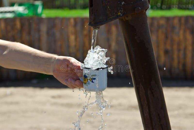 Το άτομο χύνει ένα φλυτζάνι του νερού από τη στήλη (γερανός) στοκ εικόνες με δικαίωμα ελεύθερης χρήσης