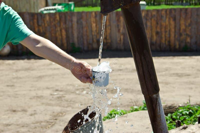 Το άτομο χύνει ένα φλυτζάνι του νερού από τη στήλη (γερανός) στοκ εικόνα με δικαίωμα ελεύθερης χρήσης
