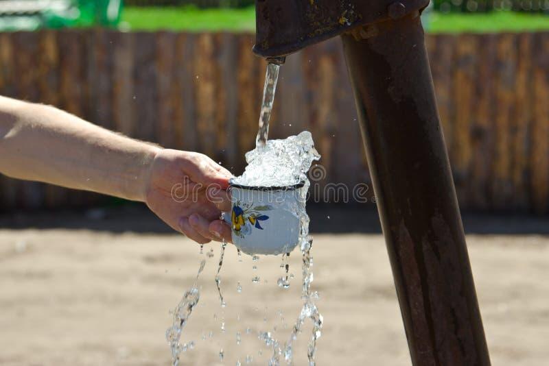 Το άτομο χύνει ένα φλυτζάνι του νερού από τη στήλη (γερανός) στοκ εικόνα