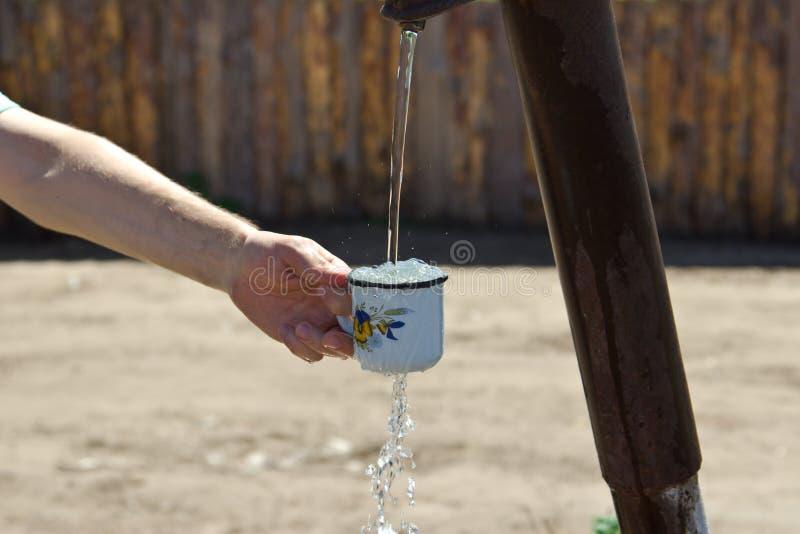 Το άτομο χύνει ένα φλυτζάνι του νερού από τη στήλη (γερανός) στοκ εικόνες
