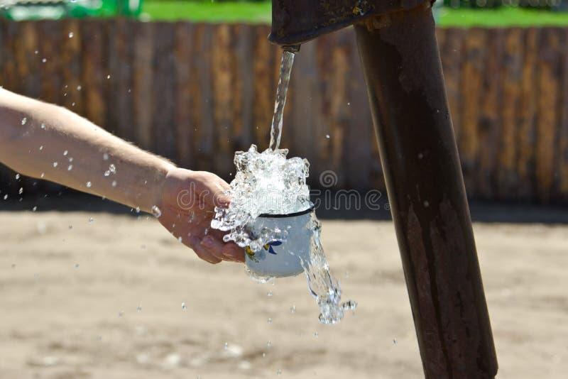 Το άτομο χύνει ένα φλυτζάνι του νερού από τη στήλη (γερανός) στοκ φωτογραφία