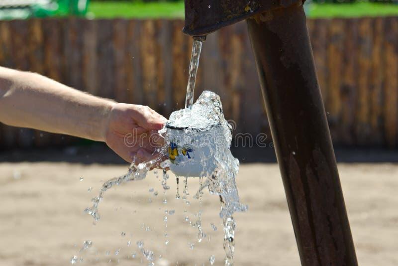 Το άτομο χύνει ένα φλυτζάνι του νερού από τη στήλη (γερανός) στοκ φωτογραφίες με δικαίωμα ελεύθερης χρήσης