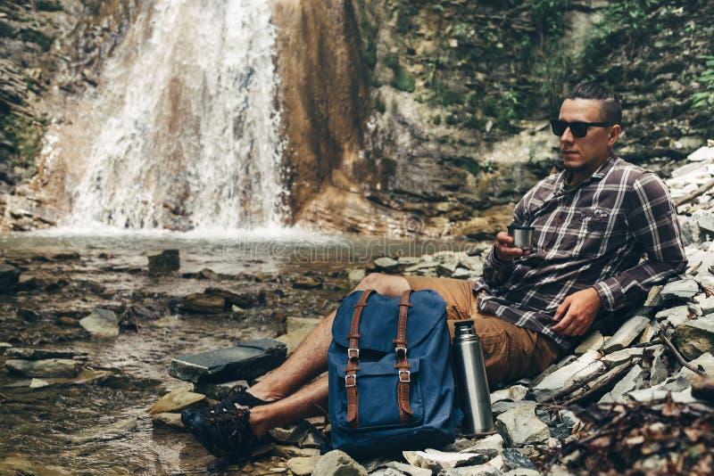 Το άτομο Backpacker πίνει το τσάι ή τον καφέ από Thermos στη στηργμένος έννοια ταξιδιού προορισμού στρατοπέδευσης υποβάθρου καταρ στοκ εικόνες