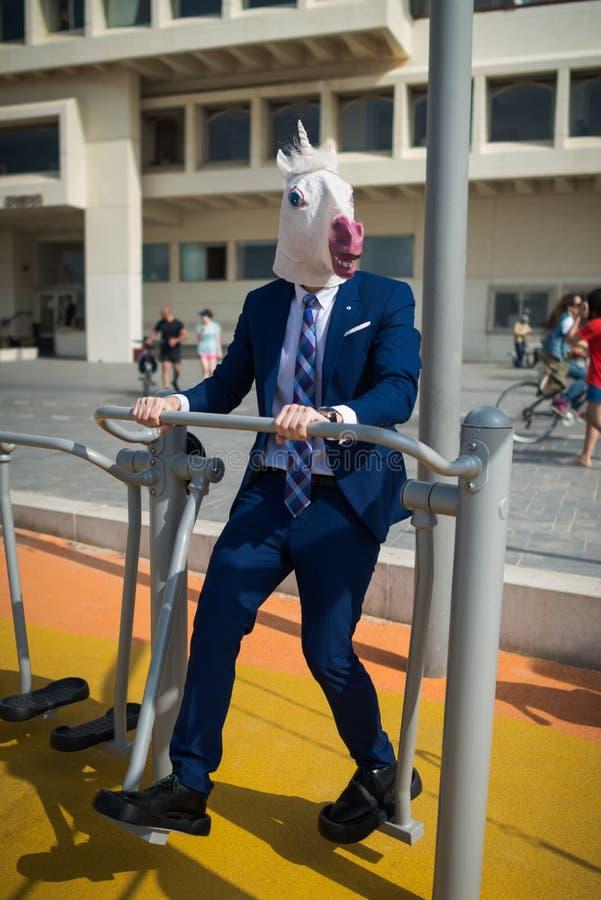 Το άτομο Freaky στο κομψό κοστούμι και την αστεία μάσκα κάνει τις αθλητικές ασκήσεις στοκ φωτογραφία με δικαίωμα ελεύθερης χρήσης