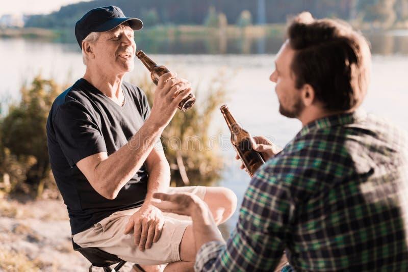 Το άτομο ` s στηρίζεται το άτομο Α πίνει την μπύρα σε ένα ταξίδι αλιείας με τον ηλικιωμένο πατέρα του Κάθονται στην όχθη ποταμού στοκ εικόνα με δικαίωμα ελεύθερης χρήσης