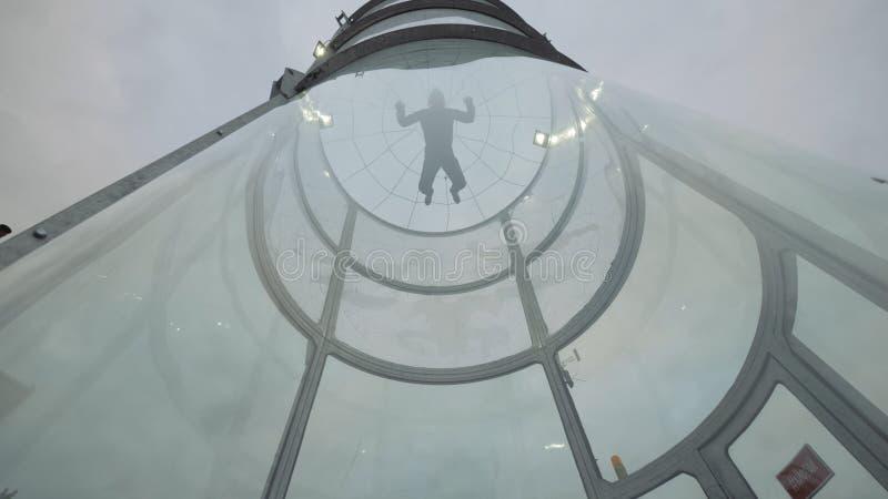Το άτομο skydiver πετά στη σήραγγα αέρα πάνω-κάτω Πέταγμα σε μια σήραγγα ελεύθερων πτώσεων με αλεξίπτωτο στοκ φωτογραφίες