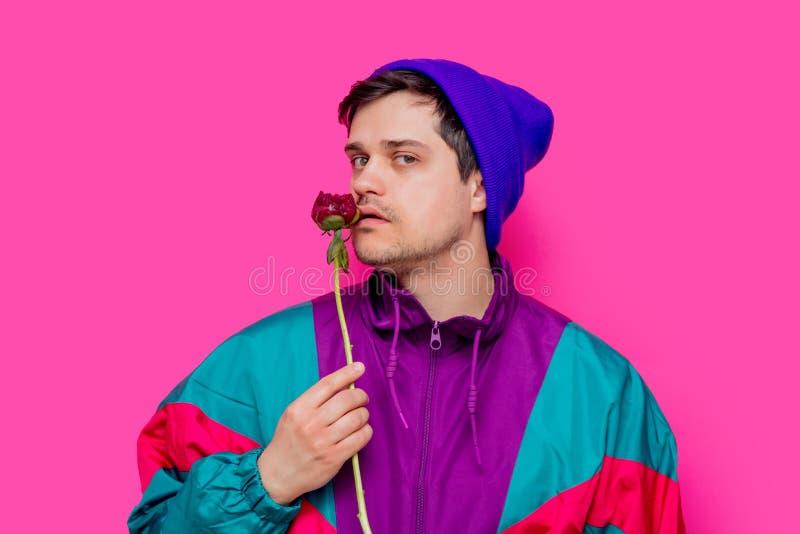 Το άτομο sniffs ενδυμάτων της δεκαετίας του '90 ανθίζει peony λουλούδι στο ρόδινο υπόβαθρο στοκ εικόνα